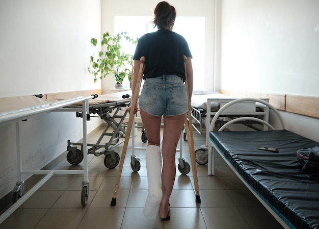 A woman with a broken leg uses orthopedic crutches leg injury rehabilitation after a fracture