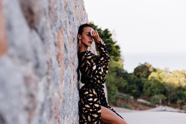 Donna con trucco in bronzo in abito nero dorato sul muro di pietra