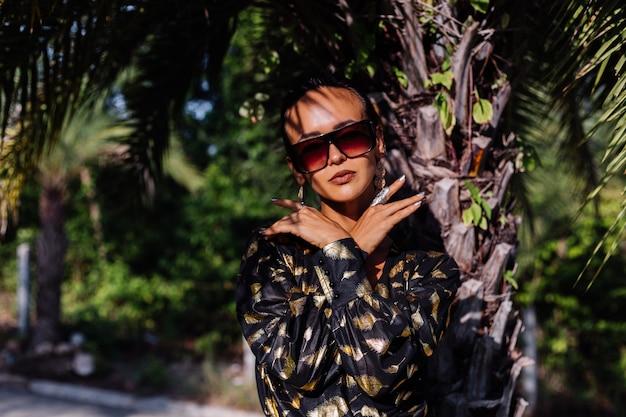 熱帯の風景の中で黒の金色のドレスとサングラスを身に着けているブロンズメイクの女性