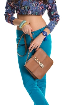 Woman with brown bag. blue pants and crop top. leather purse of high quality. set of casual accessories.
