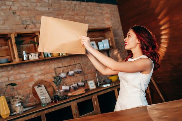 キッチンに茶色の明確な空白のクラフトペーパーバッグを持つ女性