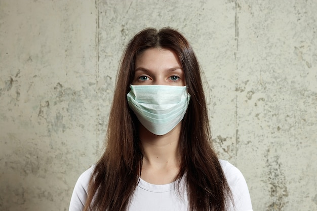 Woman with brown hair and a medical mask for protectiongain influenza