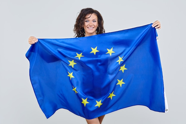Woman with brown hair posing with the european union flag in the studio on a white background