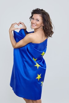 Woman with brown hair posing with the flag of the european union.