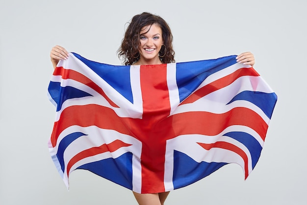 Woman with brown hair posing with the uk flag in the studio on a white background