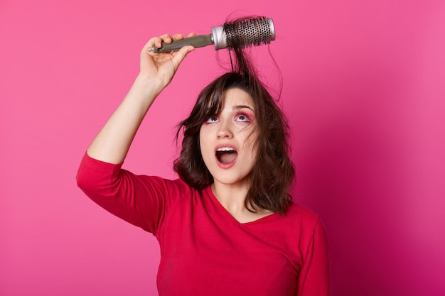Woman with brown tangled hair tries to comb hairs, looks up, wants to blow out comb and doing new hairstyle