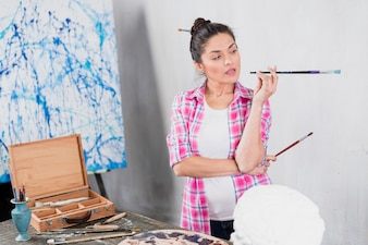 Woman with brush in art studio