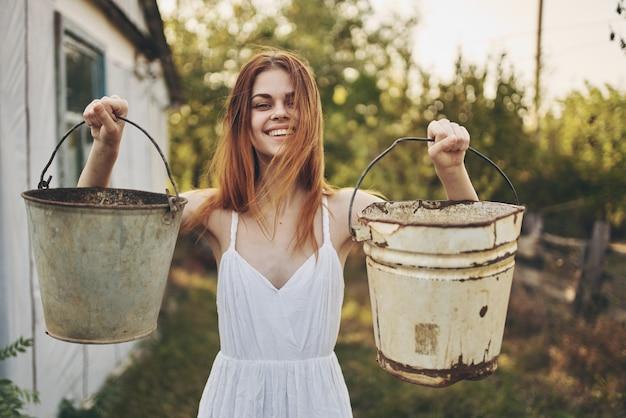 光の建物の農村の私有地の近くの屋外で手にバケツを持つ女性。