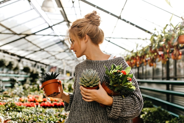 Woman with bun on her head looks at plants in shop and holds small pots with cactus, succulent with and bush with orange flowers.