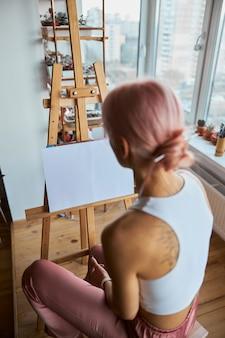 머리에 롤빵을 얹은 여자는 집에서 가벼운 발코니에 이젤 옆에 앉아 있다