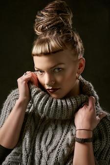 Woman with bun wearing gray sweater