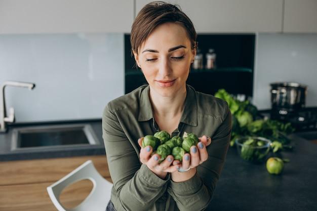キッチンで緑の野菜の束を持つ女性