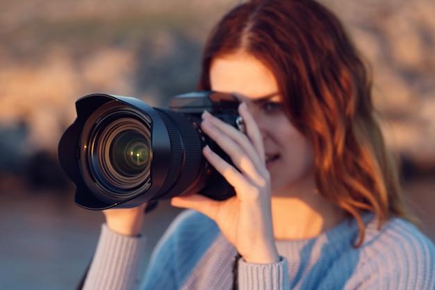 カメラと山の屋外の青いセーターを着た女性