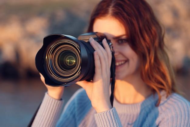 カメラと山の屋外の青いセーターを着た女性のトリミングされたビュー