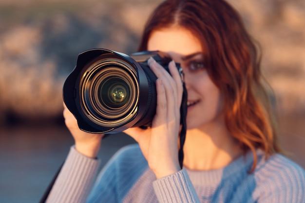 カメラを持った女性と山の中で青いセーターを着た女性