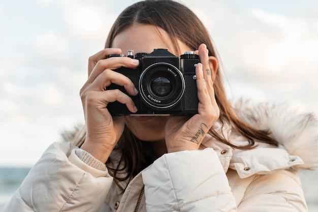 Donna con fotocamera in spiaggia
