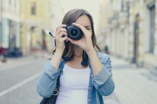 カメラの街の通りの背景を持つ女性