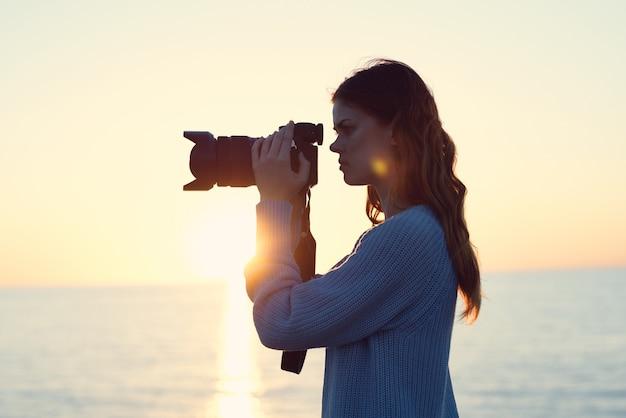 Woman with camera landscape sunset sea sun model