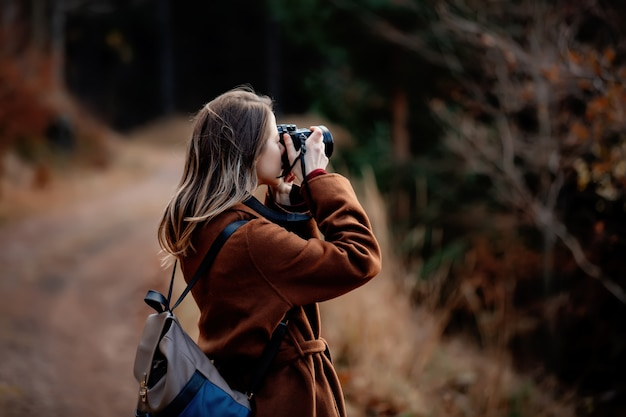 Woman with camera makes a photo in mountain forest