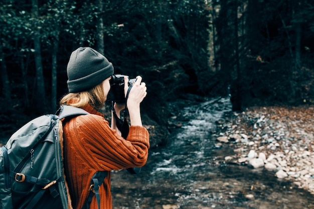 Woman with a camera on nature in the mountains near the river side view