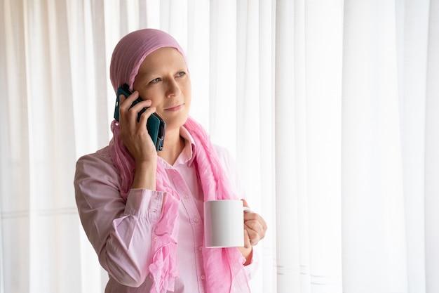 Женщина с раком и розовым платком звонит по мобильному телефону и улыбается рядом с окном