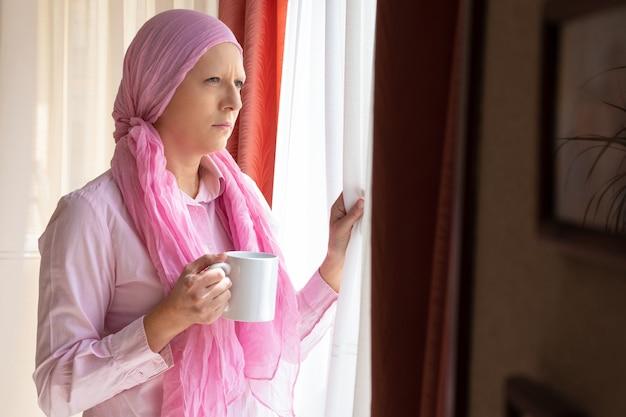 Женщина с раком и розовым шарфом на голове пьет кофе и смотрит в окно