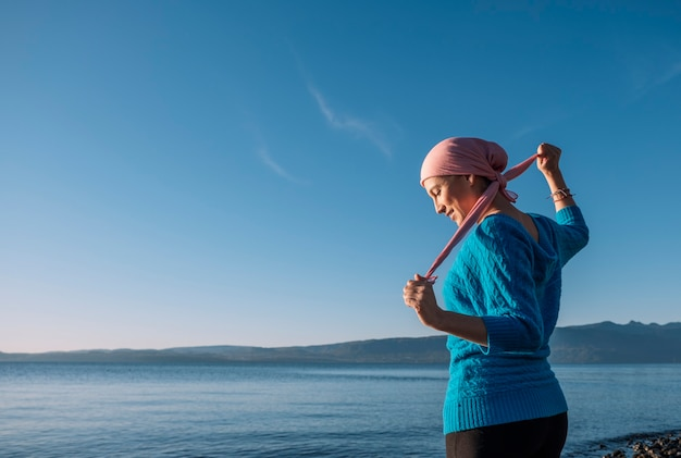 Woman with cancer at the edge of a lake tying her pink scarf on her head
