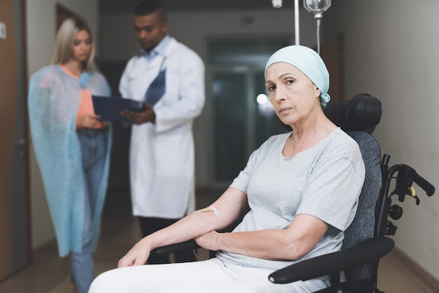 Woman with cancer is sitting. her daughter talks with doctor