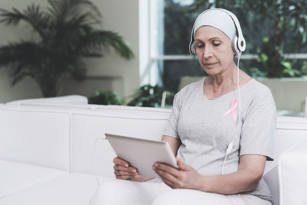Woman with cancer is sitting on sofa in a modern clinic.