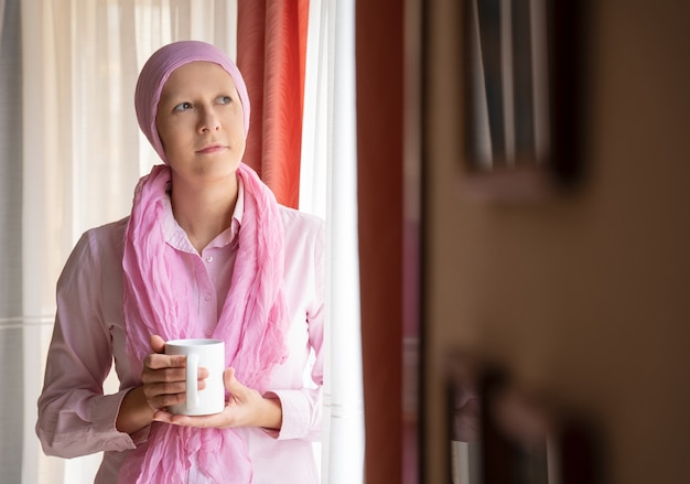 Woman with cancer and pink scarf on her head drinking coffee and looking out the window