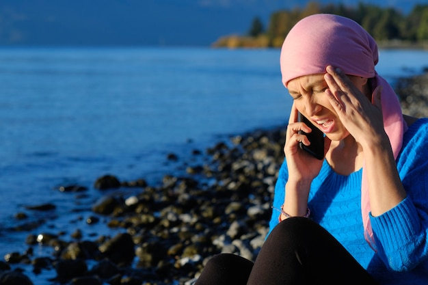Woman with cancer talking on her cell phone with a headache holding her head