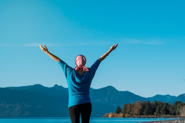 Woman with cancer wearing a pink head scarf with her arms open while looking at the sky and the lake on a beautiful day