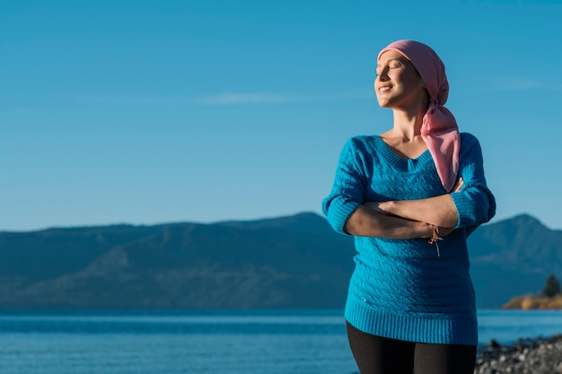 A woman with cancer wears a pink scarf on her head and stands with her arms crossed and smiling