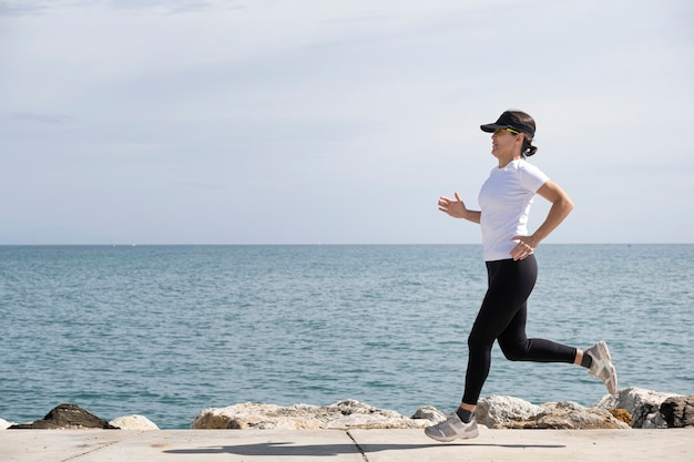 Woman with cap and sunglasses running along the promenade