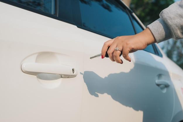 자동차 키를 가진 여자입니다. 자동차 문을 여는 중입니다. 여자의 손은 자동차의 문을 엽니다. 햇빛. 교통.
