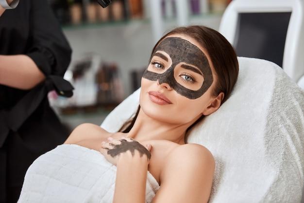 Женщина с угольной маской на лице, лежа в спа, косметические процедуры и уход за лицом