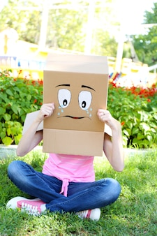 悲しい顔、屋外で彼女の頭に段ボール箱を持つ女性