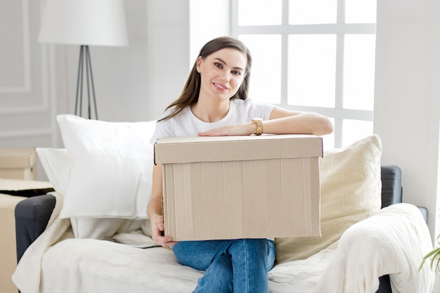 Woman with a cardboard box sitting on the sofa