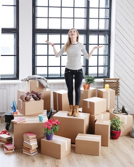 Woman with cargo packages ready to shipping or moving, feeling happy