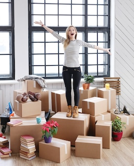 Woman with cargo packages ready to shipping or moving, standing and laughing