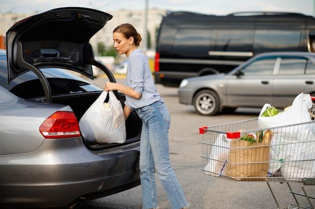 Женщина с тележкой кладет свои покупки в багажник автомобиля