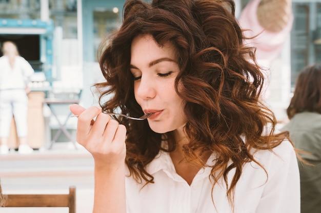 カジュアルな髪型で食事を味わい、目を閉じている女性