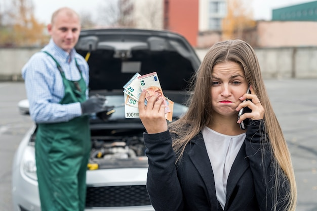 Woman with cell phone, car and mechanic