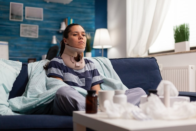 Woman with cervical neck collar sitting on sofa suffering from spine pain young caucasian person wit...