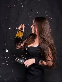 Woman with champagne bottle and glasses under spangles