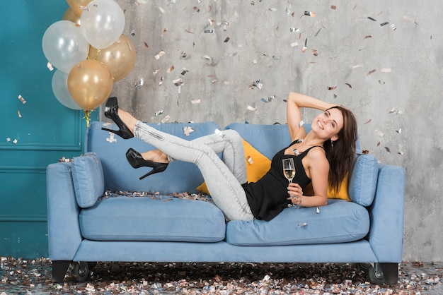 Woman with champagne on couch