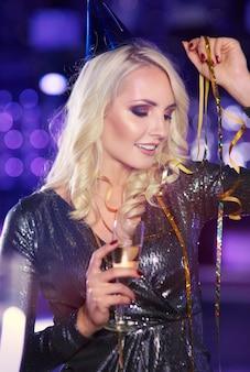 Женщина с шампанским танцует на новогодней вечеринке