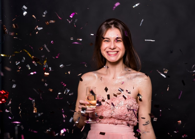 Woman with champagne glass under spangles