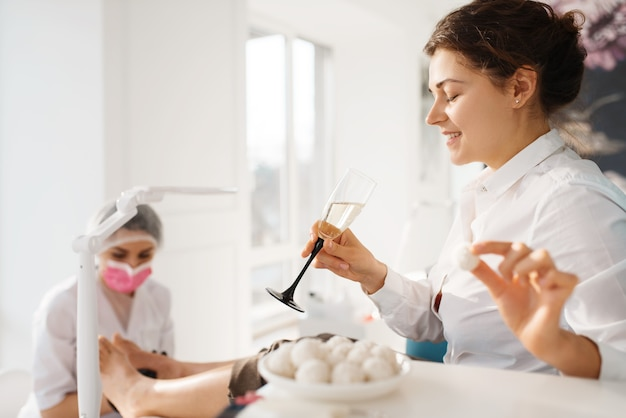 Woman with champagne relax in beauty salon, pedicure procedure.