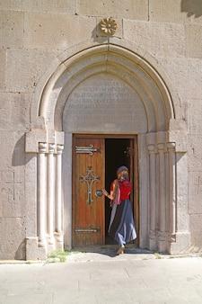 Tsakhkadzorアルメニアのkecharisのkatoghike大聖堂教会に入る礼拝堂のベールを持つ女性